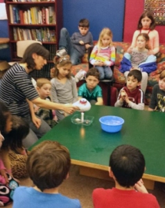 Mia Katz demonstrates a science concept to the LEAP kids.